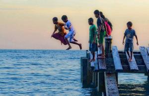 Indonesia Bambini saltano in mare vicino alla spiaggia di Susupu